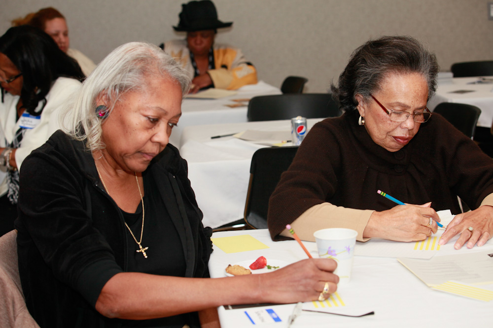 Two older ladies filling out donor forms